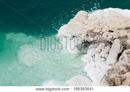 Overlooking the Dead Sea's  emerald green water and rugged, salt crusted bank. The white and tan salt crystals are bumpy and rough. Photographed from above.
