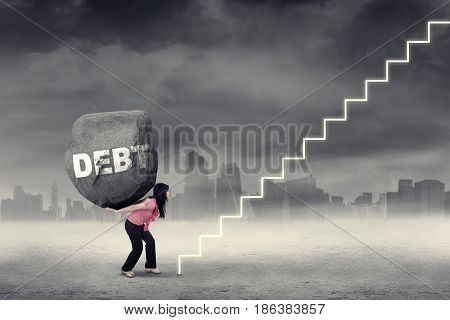Young woman carries heavy rock with Debt word on her back and climbing a stairway. Concept of big debt and difficult road