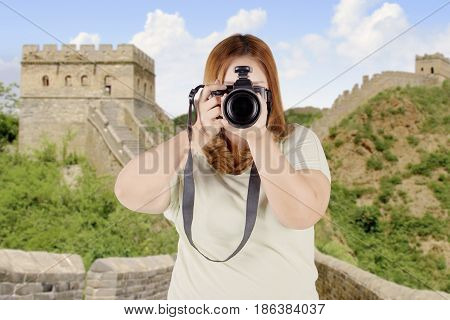Image of overweight woman using a camera to take photos while standing on the Great wall of China