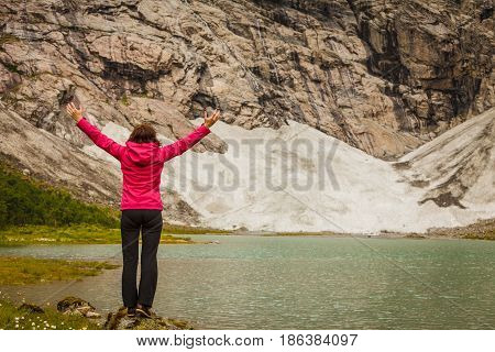 Woman With Raised Hands In Norwegian Mountains