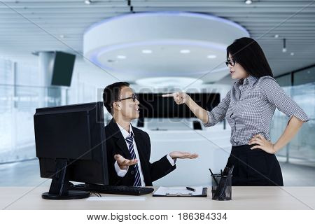 Portrait of young entrepreneur feels angry to her subordinate while standing in the office