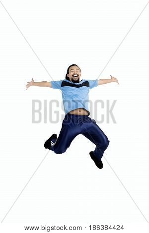 Young man wearing sportswear leaping in the studio isolated on white background