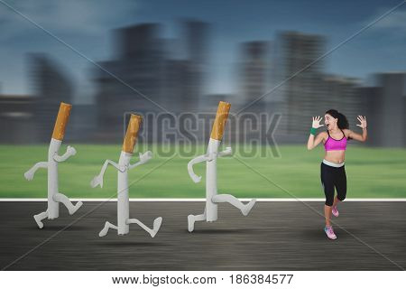 Portrait of a young woman running away by three cigarettes on the road with blur motion