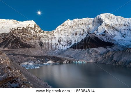 Grey Moraine Lake And Snowy Mountain Peak In The Moon Light In Himalayas, Nepal. Mirror Water Of A B
