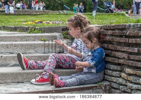 two little girls sitting on the steps outsidethe concept of having a rest children