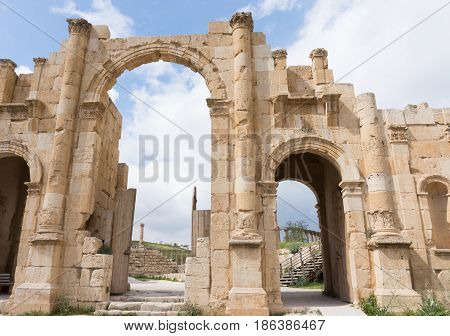 Eleven meter high three arched gate with acanthus bases, capitals at the bottom of the columns, built to honor Roman Emperor Hadrian's visit to Jerash in 129. Built with Nabataean influence.