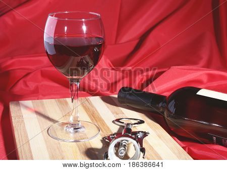 Bottle and Glass with red wine grapes and chees on wooden table