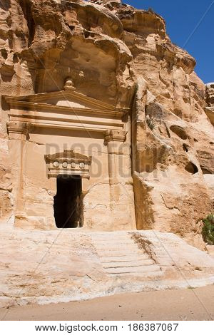 Ancient carved facade with columns and beams in relief surrounding an entrance into a tomb in Little Petra, an ancient Nabataen city in Jordan. The tomb is in a cave with steps leading to the doorway.