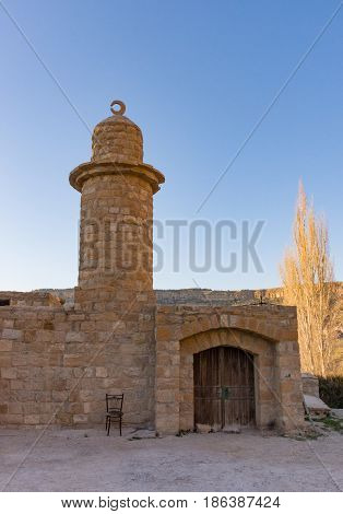 Mosque in Dana Jordan made from stones with minaret topped with crescent moon and wooden arched doorway. Background has deep blue sky and sunlit tree.