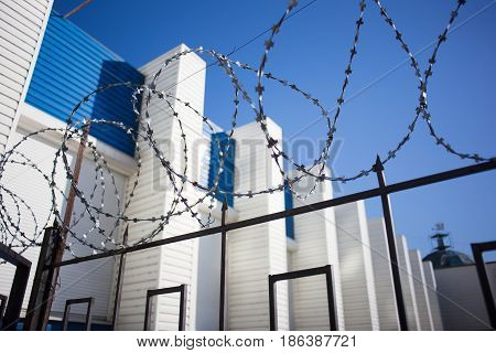 Barbed wire with white walls and blue sky