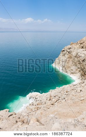 Overlooking the Dead Sea with its turquoise and aquamarine water and rugged, salt crusted bank. The horizon is hazy with blue sky and clouds above.