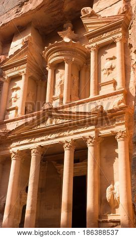 Close up of the Treasury, an ancient building in Petra, Jordan. The orange stone with columns carved by Nabataens is one of the Seven Wonders of the World and is a UNESCO World Heritage Site.