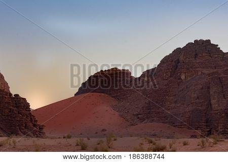 Large reddish orange sand dune swept against a rugged rocky mountain with sand in the foreground and sky at sunrise in the background. Photographed in Wadi Rum Desert, Jordan.