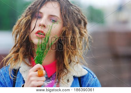 Young charming girl with dreads with a bunch of grass in his hands in a city Park on a bright day.