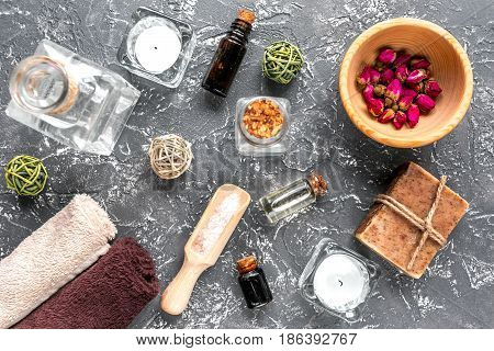spa cosmetics set with soap, salt, oil on dark desk background top view