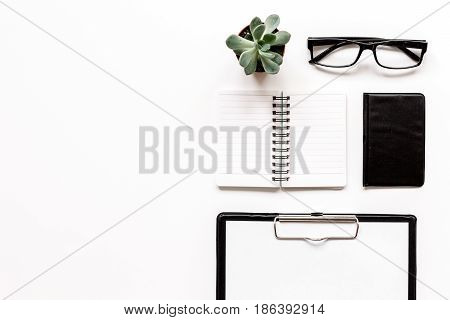 Modern office table with black wallet, glasses, notebook on white background top view mock-up