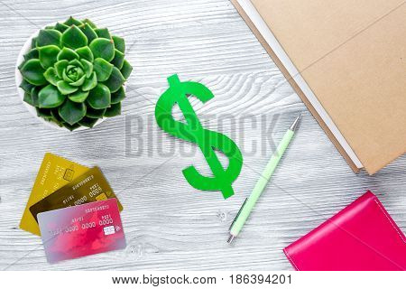 fee-paying education set with dollar sign, books and creit cards on light wooden table background top view moxkup
