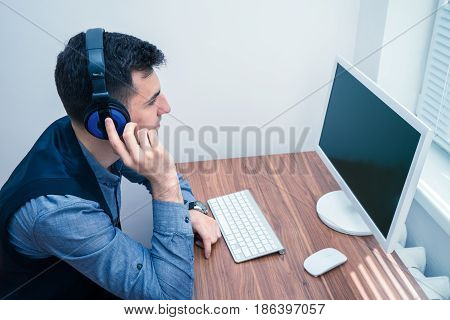 Portrait of handsome man in call center office with headphones looking at the monitor of PC computer. Copyspace on screen