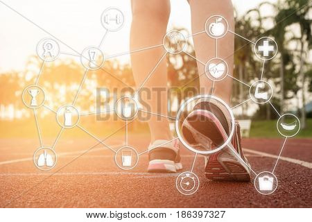 Young woman running during sunny morning on stadium track with network health icons.