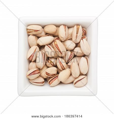 Roasted pistachio nuts in a square bowl isolated on white background