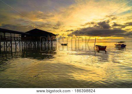 Serene sunrise beach over fishing jetty with fishing boats in fisherman village in Labuan island,Malaysia.