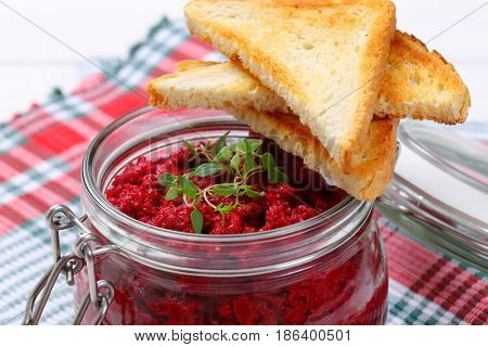 jar of fresh beetroot puree with toasts on checkered dishtowel - close up