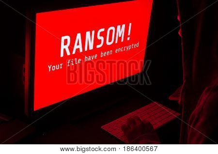 Computer screen with ransomware attack alert in red and a man keying on keyboard in a dark room ideal for online security and digital crime