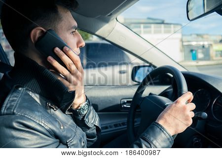 Young man using his phone while driving the car. Dangerous risky driving