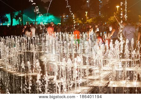 People Playing With Music Fountain
