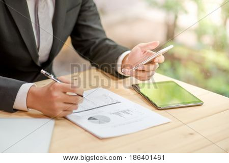 young business man in black suit checking summary report graph and using smartphone for calculate data analysis smart working and good potential management with digital device in office workspace