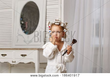 Little girl fashionista. A girl in a curler and a robe is holding a makeup brush. Little coquette posing. Human emotions. She is distressed.