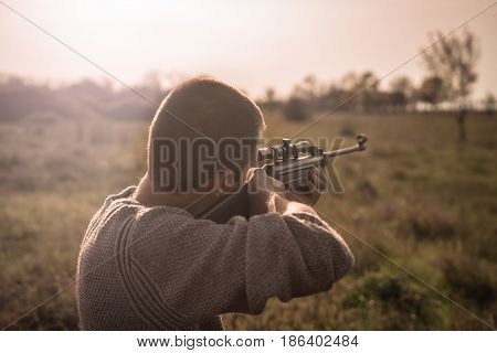 The man takes aim at the target with a sniper strikeball rifle during sunset. Selective Focus. Retro film toning.
