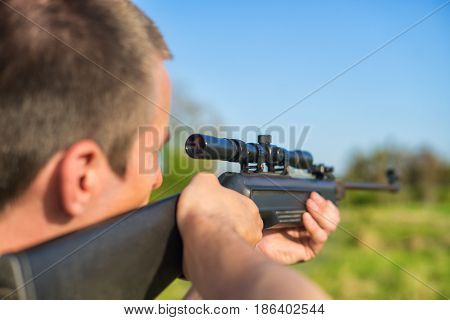 The man takes aim at the target with a sniper strikeball rifle. Selective Focus. Blue sky.