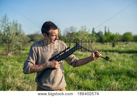 The man recharges sniper rifle outdoor. Selective Focus. Green grass and blue sky on background