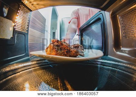 Man putting grilled chicken into microwave oven. inside view