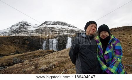 Asian Retired Senior Travel Around The World To Iceland. Happy Together At Kirkjufell Mountain