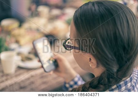 Smart girl wearing glasses using mobile phone while eating. Selective focus with bokeh. Retro toning