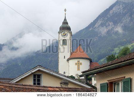 Church of Fluelen in front of foggy mountain ridges at Lake Luzern Switzerland
