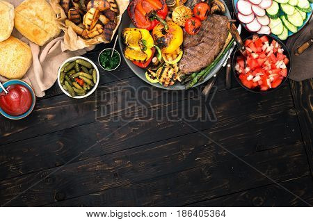 Different foods cooked on the grill grilled steak and grilled vegetables on the wooden table with border. Top view. Outdoors Food Concept