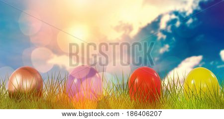 Mulit colored Shiny Easter eggs on grass against blue sky