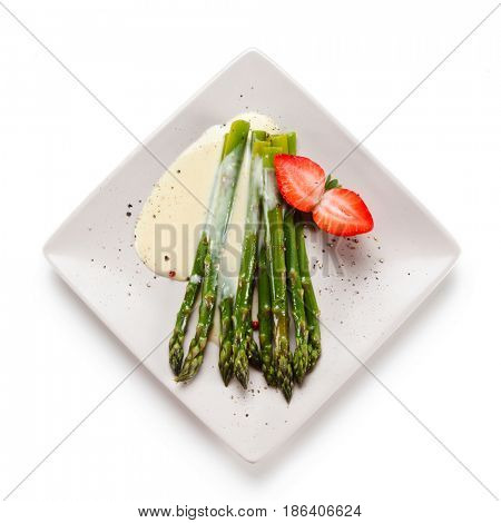 Grilled asparagus with sauce on white plate