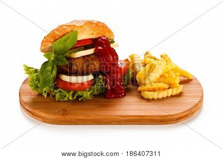 Hamburger with french fries on cutting board