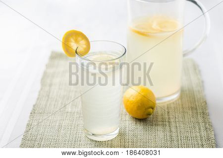 Lemonade glass and pitcher. Lemonade is traditionally a homemade drink made with squeezed lemon water and sugar a simple recipe for a quick refreshing summer drink packed with vitamin c.