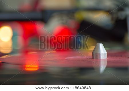 A turntable playing music vinyl record. Focused on tonearm needle platter vinyl record. Colorful lights blurred in background with reflections at the vinyl.