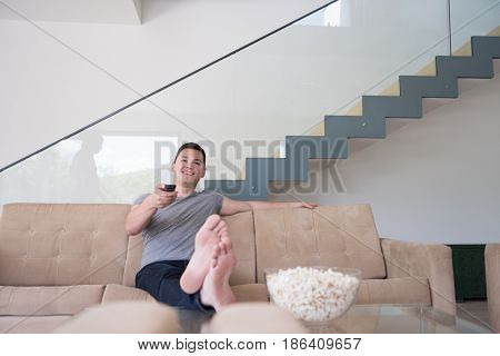 young handsome man enjoying free time watching television with popcorn in his luxury home villa