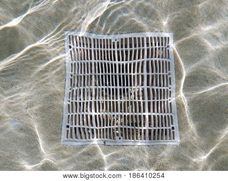 water and distorted pool drain in shallow water