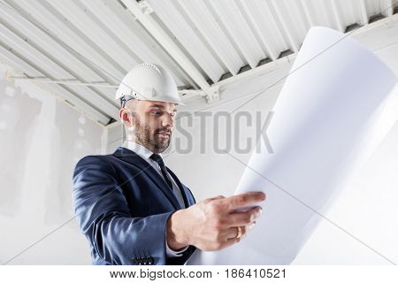 Business investor checking documents at the construction site. Housing development and building industry.