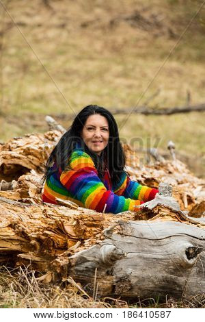 Smiling woman sittin in middle of bark trees and posing