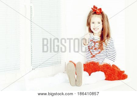 Beautiful little girl a bright red bow on head and red skirt sitting by the window. She holds a thumb up. Creative toning of a photograph.