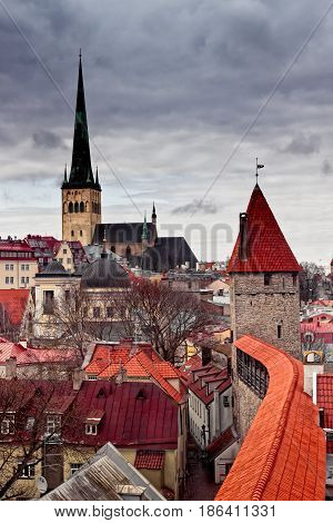 The tower of the St. Olaf's church rises to the dramatic clouds over the old town of Tallinn Estonia. The church was built in the 12th century.